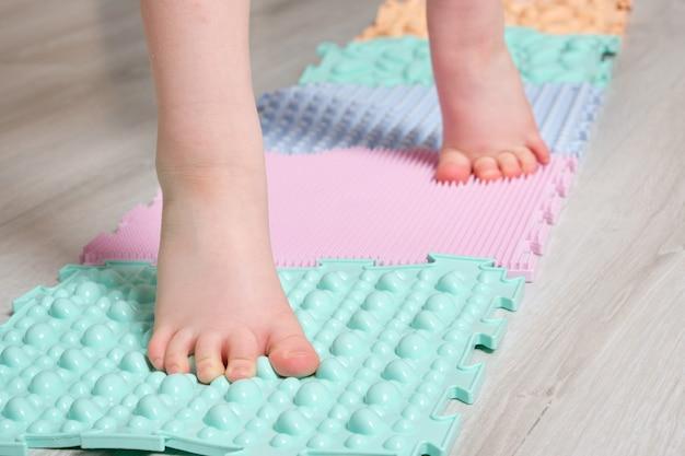 L'enfant masse les pieds avec un tapis orthopédique