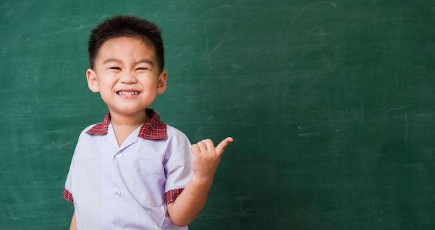 Enfant de la maternelle en uniforme d'étudiant souriant sur tableau noir école verte
