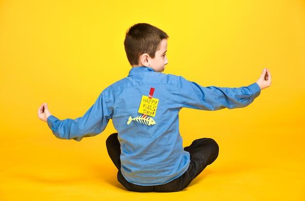L'enfant médite engagé dans l'inscription de yoga le jour du fou