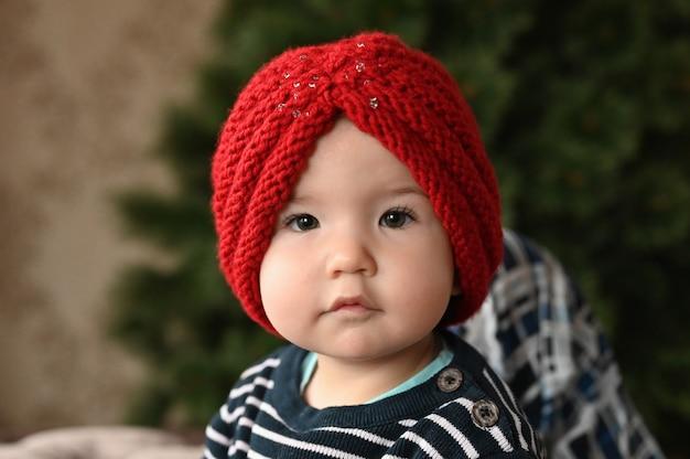 Un enfant met un chapeau. un chapeau rouge et un enfant. montre un doigt. l'enfant a 0-1 ans. portrait d'enfant d'un an.