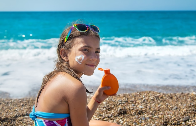 L'enfant met de la crème solaire sur son visage. mise au point sélective. enfant.