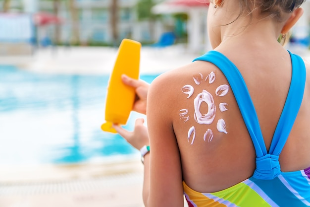 L'enfant met de la crème solaire