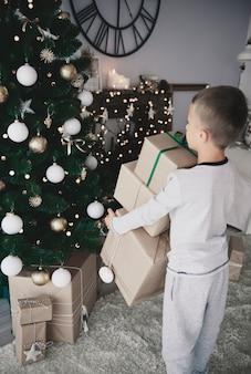 Enfant mettant des cadeaux sous un arbre de noël