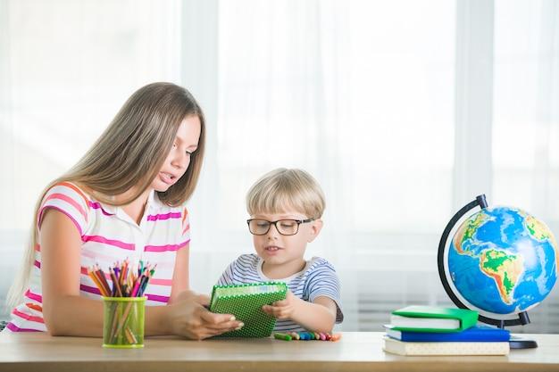 Enfant mignon apprenant une leçon avec sa mère. famille faisant ses devoirs ensemble. mothe expliquant à son petit écolier comment faire une tâche.
