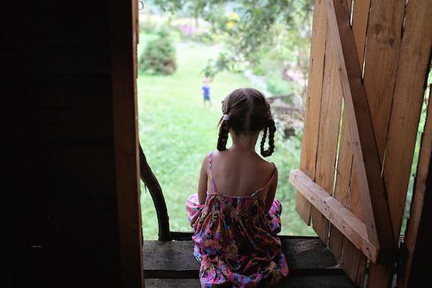 Enfant mignon assis seul dans la cabane en été