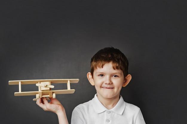 Enfant mignon avec avion en bois