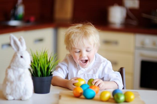 Enfant mignon bambin à la recherche d'oeufs de pâques le jour de pâques