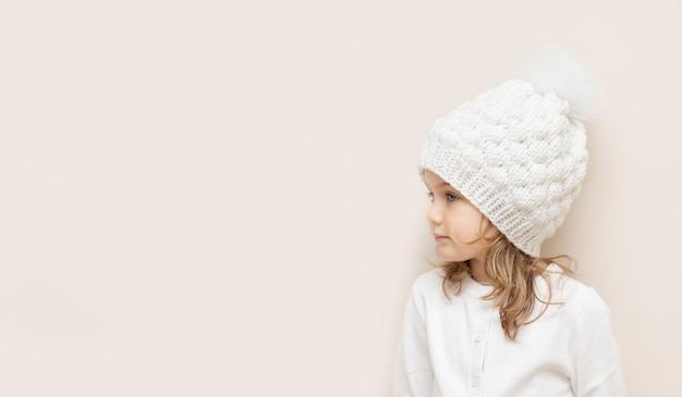 Enfant mignon en bandeau tricoté en laine fait main et pull blanc isolé sur fond beige