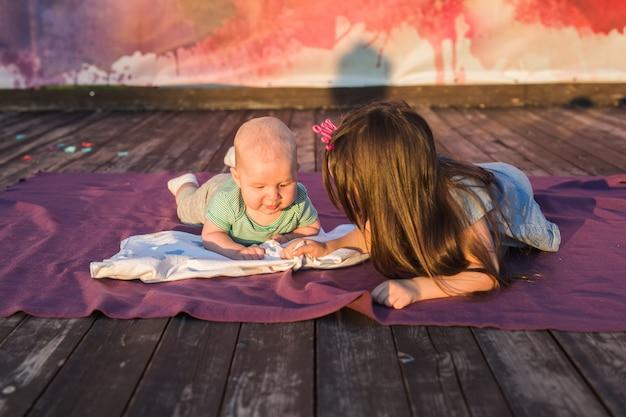 Enfant mignon bébé garçon et petite fille allongée sur une couverture en journée d'été sur la nature. frère et soeur