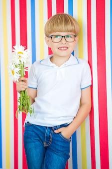 Enfant mignon bouchent portrait sur coloré. adorable petit garçon debout près du mur. enfant tenant un bouquet de fleurs.