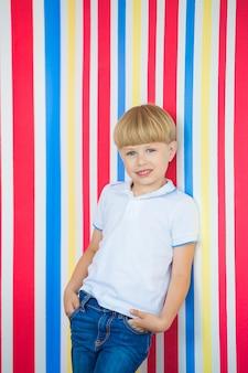 Enfant mignon bouchent portrait sur coloré. adorable petit garçon debout près du mur.