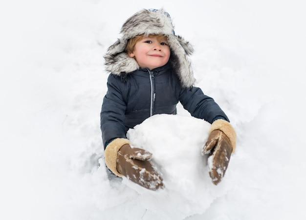 Enfant mignon debout dans un chapeau d'hiver avec nez rouge.