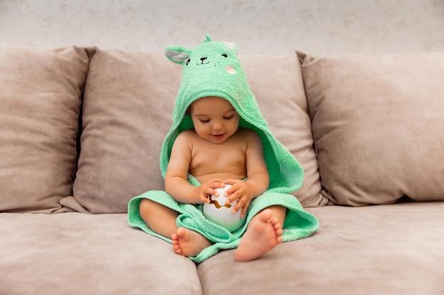 Un enfant mignon enveloppé dans une serviette est assis sur le lit. bébé dans une serviette de bain.
