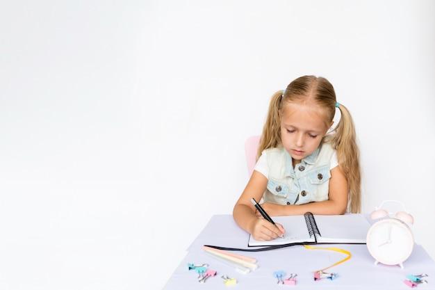 Enfant mignon fait ses devoirs sur fond blanc.