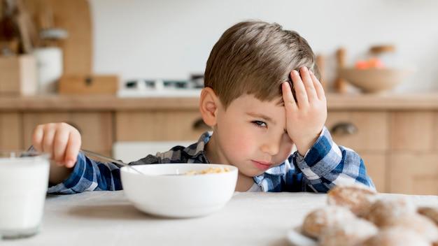 Enfant mignon fatigué au petit déjeuner