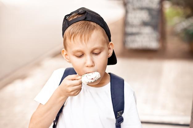Enfant mignon de garçon d'enfant mangeant la crème glacée en plein air dans un parc