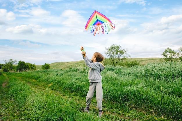 Enfant mignon jouant avec un cerf-volant coloré en plein air