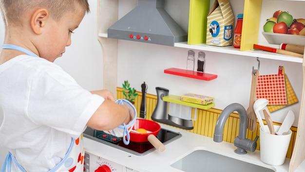Enfant mignon jouant avec un jeu de cuisine