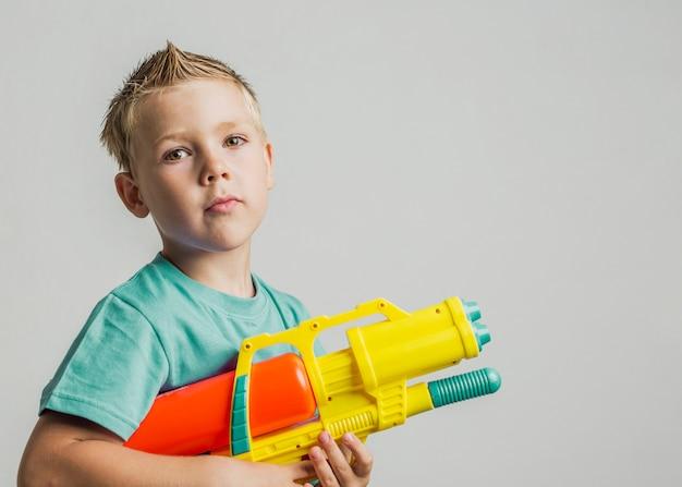 Enfant mignon jouant avec un pistolet à eau