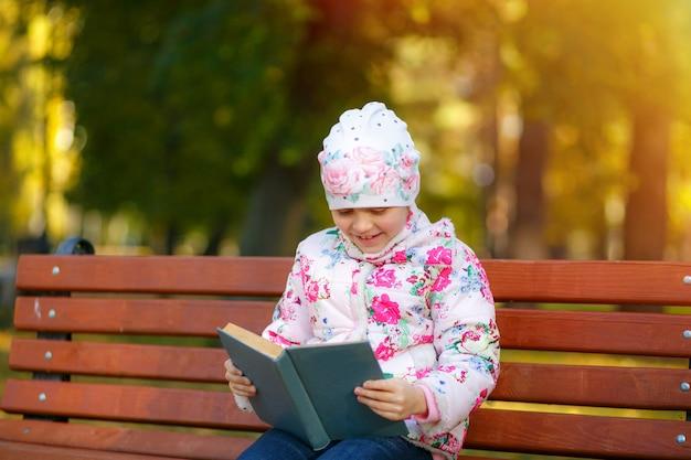 Un enfant mignon lit un livre dans le parc.