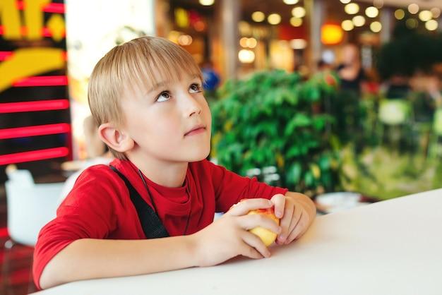 Enfant mignon mangeant une pomme dans un café moderne