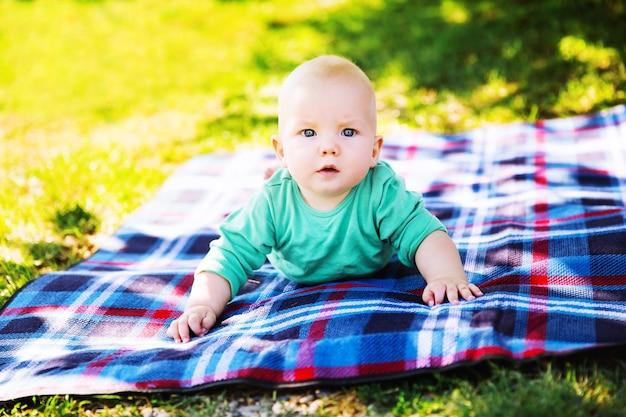Enfant mignon petit garçon allongé sur une couverture en journée d'été sur la nature. sourire heureux, 6 mois, extérieur. pique-nique familial dans un parc.