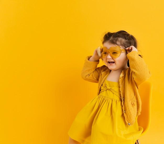 Enfant mignon posant tout en portant des lunettes de soleil