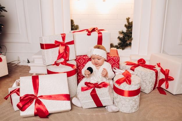 Enfant mignon en robe blanche, posant sous l'arbre de noël.