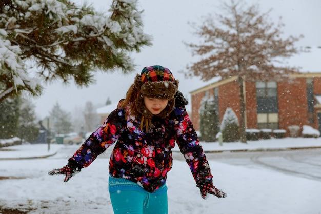Enfant mignon s'amuser sous la neige de l'hiver