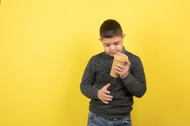 Enfant mignon avec le syndrome de down buvant une tasse de café sur jaune.