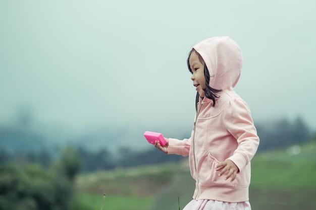 Enfant mignonne petite fille courir dans le jardin après la pluie