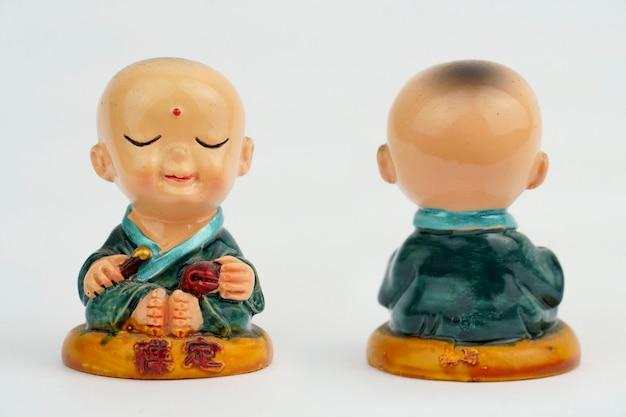 L'enfant mini bouddha sourit paisiblement. mini statue de moine avec manteau vert isolé sur fond blanc. avant et arrière.