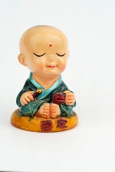 L'enfant mini bouddha sourit paisiblement. mini statue de moine avec manteau vert isolé sur fond blanc. verticale.