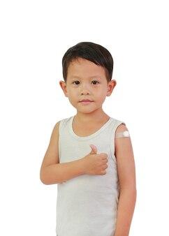L'enfant montre le pouce pour le bras avec un pansement adhésif, du coton de vacciné. petit garçon asiatique avec du plâtre sur l'épaule de l'injection. traitement des enfants patch. notion de vaccination