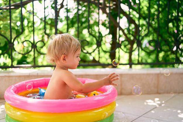 Enfant mouillé assis dans une petite piscine gonflable et attrapant des bulles de savon