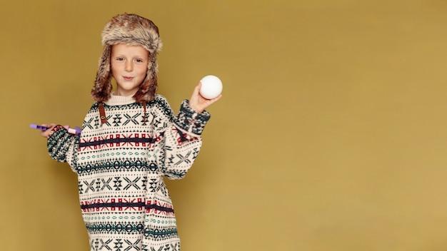 Enfant moyen tir avec boule de neige et copie espace