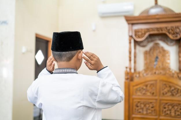 Enfant musulman priant dans la mosquée
