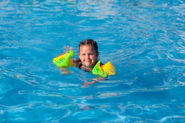 L'enfant nage dans la piscine charmante petite fille en brassards gonflables apprend à nager par une chaude journée d'été ...