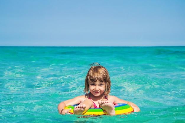 Un enfant nage dans une piscine avec un gilet de sauvetage.