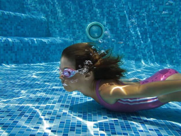 Enfant nage dans la piscine sous l'eau
