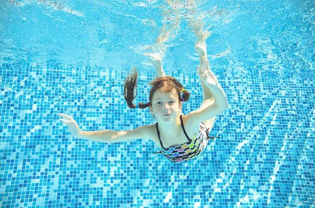 Enfant nage sous l'eau dans la piscine, une adolescente active heureuse plonge et s'amuse sous l'eau, la remise en forme et le sport pour les enfants en vacances en famille sur la station