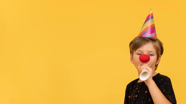Enfant avec nez de clown et espace copie
