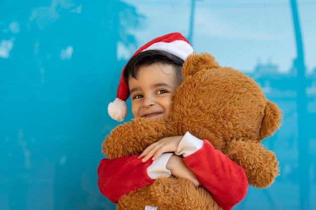 Enfant à noël avec fond bleu ours en peluche