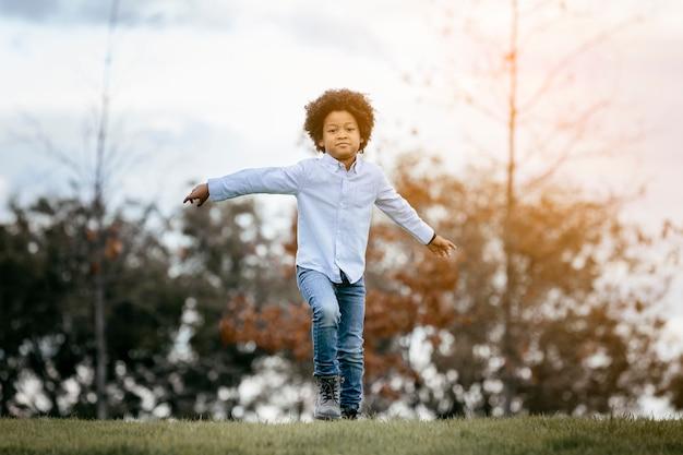 Enfant noir aux cheveux afro, courant dans un parc