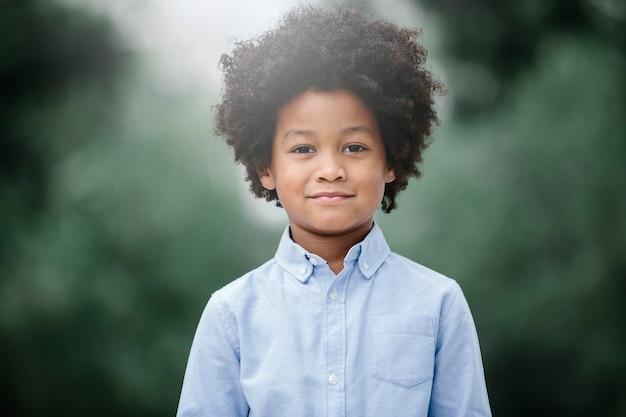 Enfant noir aux cheveux afro, souriant dans un parc