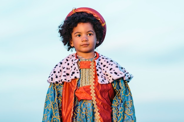 Enfant noir aux cheveux afro, vêtu d'un costume de sage. regarder ailleurs. dans un fond de ciel. coup moyen. enfants et concept de noël.