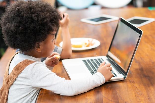 Enfant noir jouant à l'ordinateur au bureau, l'apprentissage et l'éducation