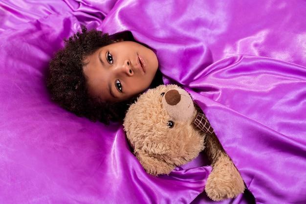 Enfant noir avec ours en peluche. enfant au lit avec ours en peluche. ferme tes yeux. ne vous inquiétez pas, vous êtes chez vous.