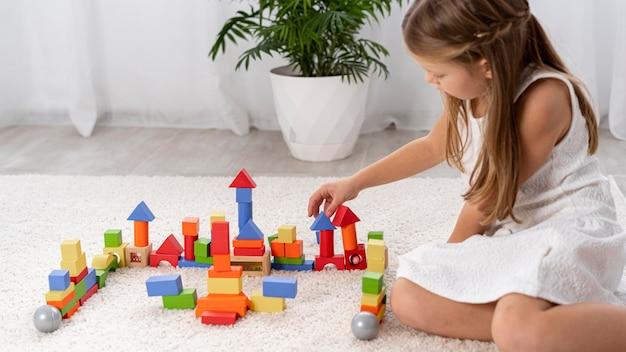 Enfant non binaire jouant avec un jeu coloré à la maison