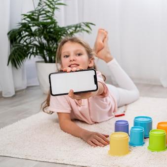 Enfant non binaire tenant un téléphone vierge